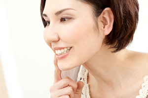 鏡で歯茎を見る女性
