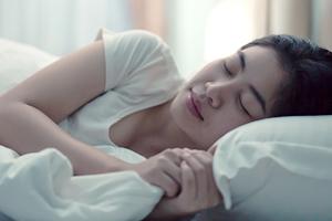 寝ている間に歯ぎしりや食いしばりをする女性